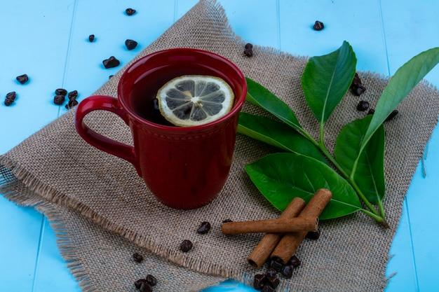 青の背景に荒布を着たレモンスライスとシナモンの葉とチョコレートの部分とお茶のカップの側面図 無料写真