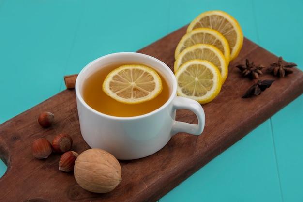 青い背景のまな板にレモンスライスとシナモンナッツクルミとお茶の側面図 無料写真
