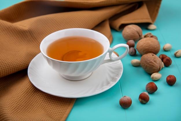 Вид сбоку на чашку чая с грецкими орехами, лесными орехами с фисташками с коричневым полотенцем на бирюзовой поверхности Бесплатные Фотографии