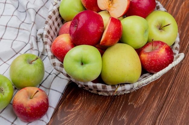 Вид сбоку нарезанных и целых яблок в корзине и на клетчатой ткани на деревянной поверхности Бесплатные Фотографии