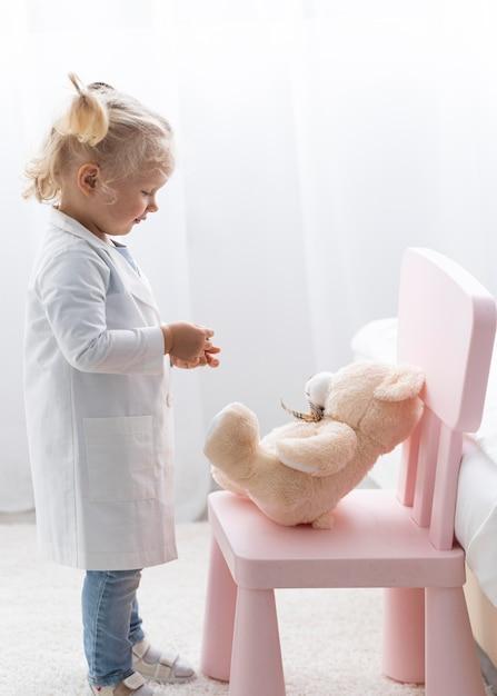 실험실 코트와 테디 베어와 함께 귀여운 유아의 측면보기 무료 사진