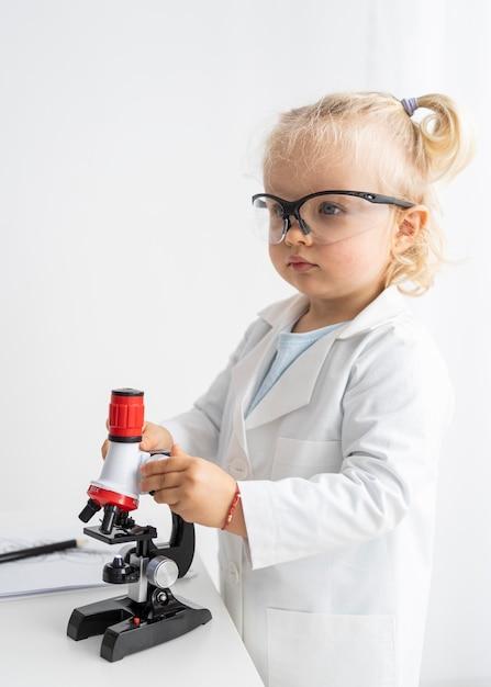 현미경 및 안전 안경으로 귀여운 유아의 측면보기 프리미엄 사진