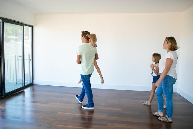 Вид сбоку на папа, держащего дочь и идущего с ней на балкон Бесплатные Фотографии