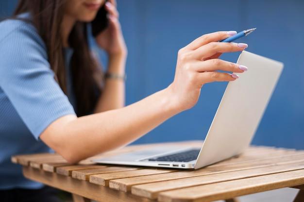 Вид сбоку расфокусированным женщина работает на ноутбуке во время разговора на смартфоне Premium Фотографии