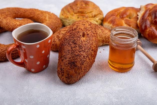 ガラスの瓶にお茶と蜂蜜のカップと白い背景で隔離のさまざまなパンとおいしいゴマのパテの側面図 無料写真