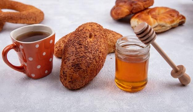 白い背景の上のガラスの瓶にお茶と蜂蜜のカップとおいしいゴマパテの側面図 無料写真