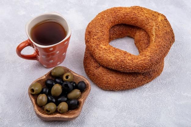 白い背景の上の木製のボウルにお茶とオリーブのカップとおいしいゴマトルコベーグルの側面図 無料写真