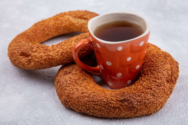 白い背景の上のお茶とおいしいゴマトルコベーグルの側面図 無料写真