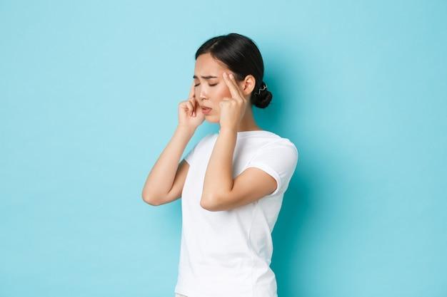 Вид сбоку на головокружение, стресс или истощение молодой азиатской женщины, которая плохо себя чувствует, закрывает глаза и массирует виски, у нее головная боль, жалуется на мигрень, стоит синяя стена Premium Фотографии