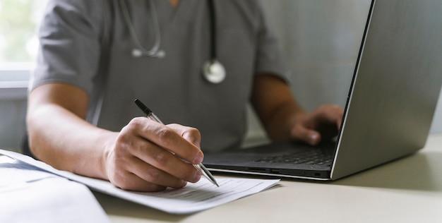 Вид сбоку на врача со стетоскопом, работающего на ноутбуке и пишущего на бумаге Бесплатные Фотографии