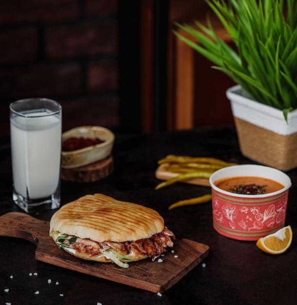 Вид сбоку донер-кебаб в лаваше на деревянной доске, подается с айранским напитком из супа липы и маринованным острым зеленым перцем на деревянной стене Бесплатные Фотографии