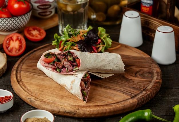 Вид сбоку донер кебаб, завернутый в лаваш со свежим салатом на деревянной доске Бесплатные Фотографии