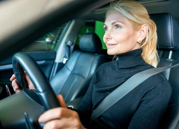 車を運転する高齢者のビジネス女性の側面図 無料写真