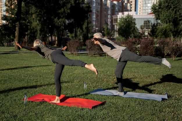 Вид сбоку пожилой пары, практикующей йогу на открытом воздухе Premium Фотографии