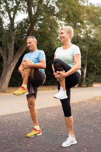 屋外で運動する前にウォーミングアップする老夫婦の側面図 無料写真