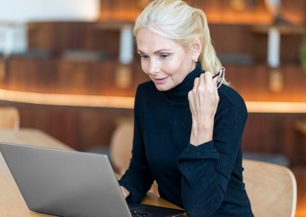 Вид сбоку пожилой женщины в очках, работающих на ноутбуке Бесплатные Фотографии