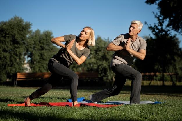 Вид сбоку пожилой пары, практикующей йогу снаружи Premium Фотографии