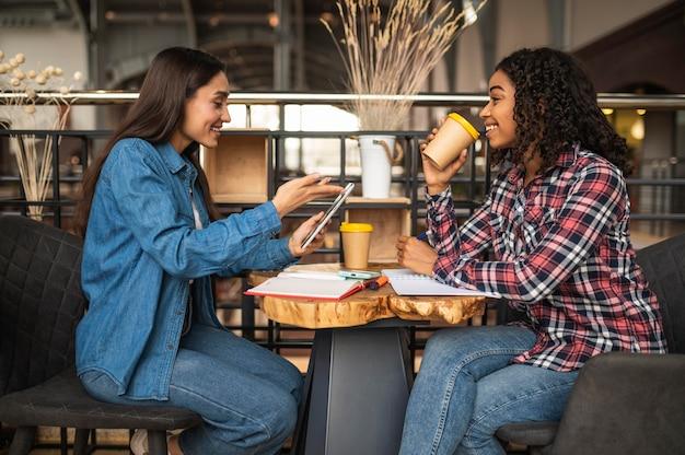 Вид сбоку подруги, делающей домашнюю работу в кафе, выпивая Premium Фотографии