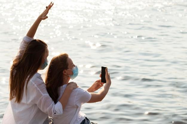 Вид сбоку подруги в масках, делающей селфи на берегу озера Бесплатные Фотографии