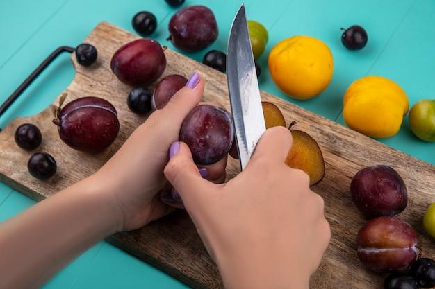 まな板にナイフとブドウの果実でプルオットを切る女性の手の側面図と青い背景のブドウネクタコットプラムプルオットのパターン 無料写真