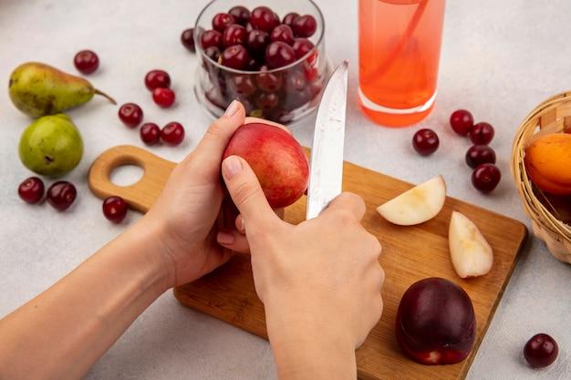 まな板にナイフで桃とチェリーの瓶と白い背景の上の梨とアプリコットのバスケットとチェリージュースをスライスする女性の手の側面図 無料写真