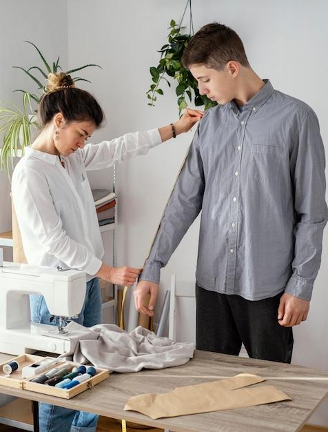 男性のクライアントのシャツを測定する女性の仕立て屋の側面図 無料写真