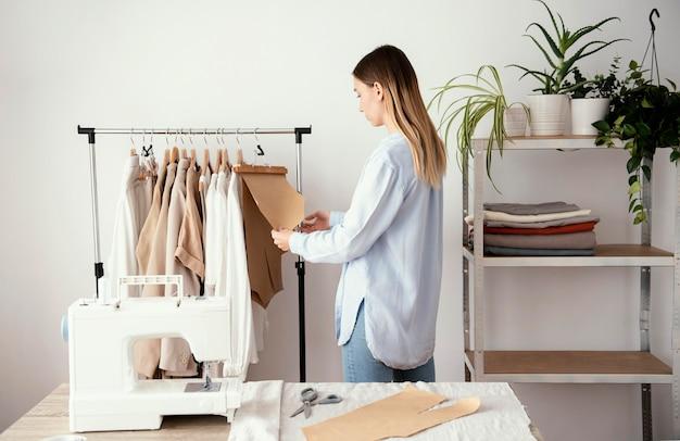 衣服の生地を準備する女性の仕立て屋の側面図 無料写真