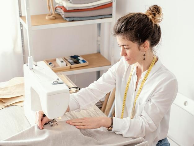 スタジオで働く女性の仕立て屋の側面図 無料写真