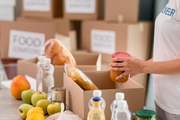 Вид сбоку на упаковочные коробки женщин-добровольцев с пожертвованиями на еду Premium Фотографии