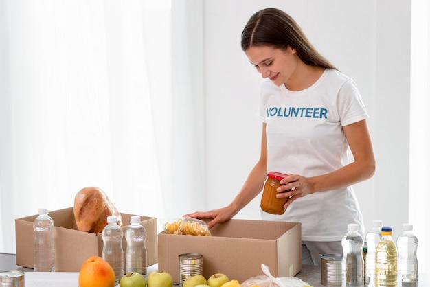 Вид сбоку на женщину-добровольца, упаковывающую еду в коробки для пожертвований Бесплатные Фотографии