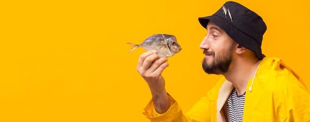 コピースペースでキャッチを保持している漁師の側面図 無料写真
