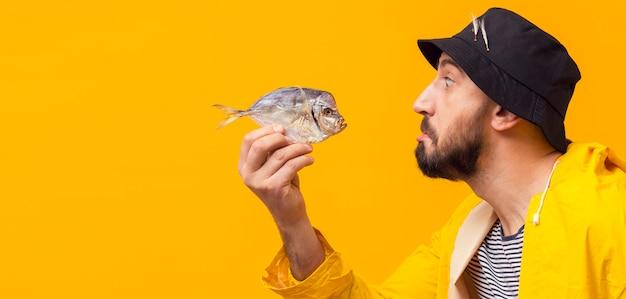 コピースペースを持つ魚を保持している漁師の側面図 無料写真