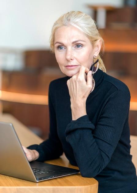 Вид сбоку сосредоточенной пожилой женщины в очках, работающей на ноутбуке Бесплатные Фотографии