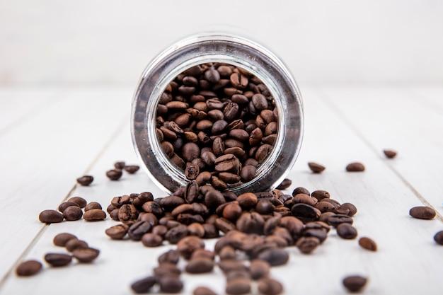 Вид сбоку свежих кофейных зерен, падающих из стеклянной банки на белом деревянном фоне Бесплатные Фотографии