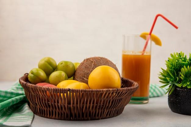 Вид сбоку на свежие фрукты, такие как зеленые вишневые сливы, желтые персики на ведре со свежим персиковым соком на стакане на белом фоне Бесплатные Фотографии