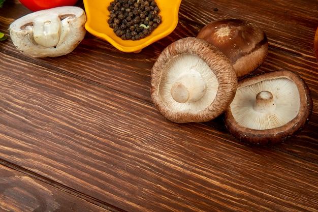 Вид сбоку свежих грибов и черного перца на деревенском дереве с копией пространства Бесплатные Фотографии