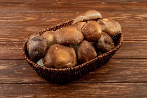 Вид сбоку свежих грибов в плетеной корзине на деревенском дереве Бесплатные Фотографии