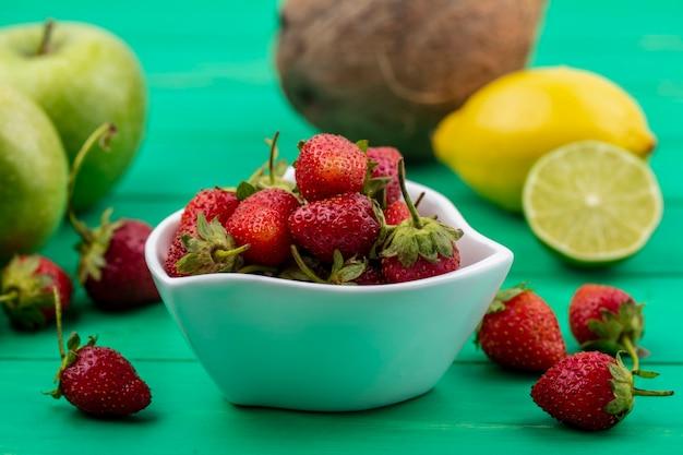 Вид сбоку свежей красной клубники на белой миске с лимоном и яблоком на зеленом фоне Бесплатные Фотографии