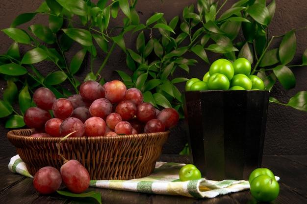 Вид сбоку свежего сладкого винограда в плетеной корзине и миску с кислыми зелеными сливами на деревянной поверхности на столе зеленые листья Бесплатные Фотографии