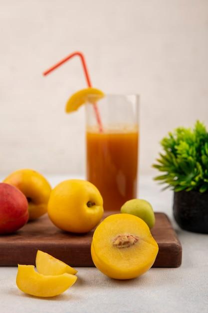 白い背景の上の桃ジュースと木製のキッチンボード上の新鮮な甘い黄色の桃の側面図 無料写真