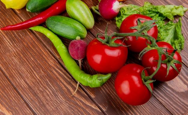 素朴な木の新鮮な野菜の完熟トマトきゅうり青唐辛子と大根の側面図 無料写真