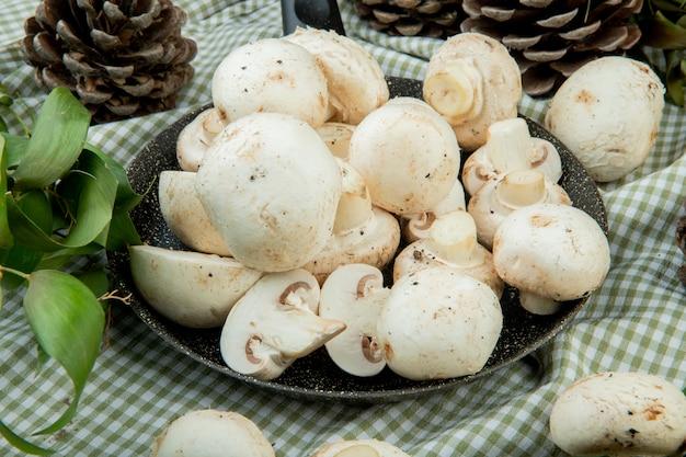Вид сбоку свежих белых грибов на сковороде и шишки с зелеными листьями на клетчатой ткани Бесплатные Фотографии