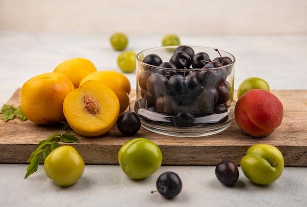 白い背景の上のガラスのボウルに濃い紫色のスローと木製のキッチンボード上の新鮮な黄色の桃の側面図 無料写真