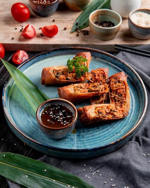 黒のプレートに鶏肉と野菜の醤油炒め春巻きの側面図 無料写真