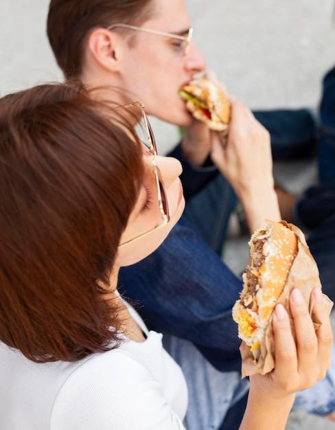 屋外でハンバーガーを食べる友人の側面図 無料写真
