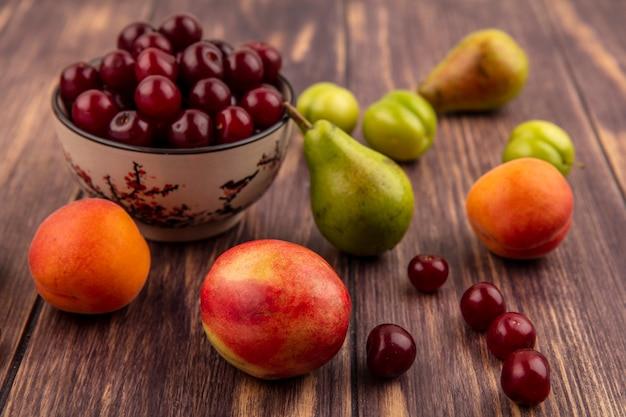 ボウルにさくらんぼとしての果物の側面図と木製の背景に桃梅アプリコット梨さくらんぼのパターン 無料写真
