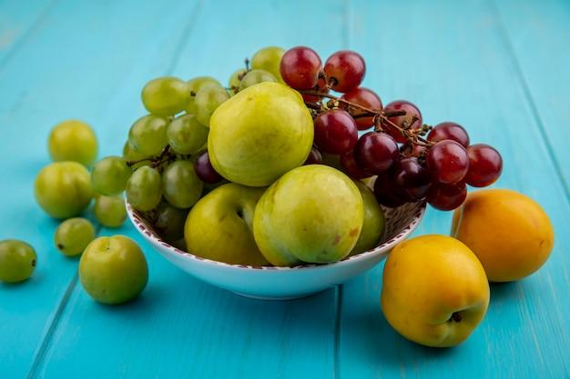 ボウルにブドウの緑のプルオットとして果物の側面図と青い背景に梅とネクタコットのパターン 無料写真