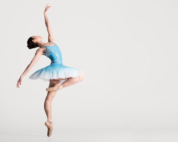 Вид сбоку грациозных балерина танцует с копией пространства Premium Фотографии