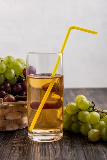 Вид сбоку виноградного сока в стекле и винограда в корзине и на деревянной поверхности и белом фоне Бесплатные Фотографии