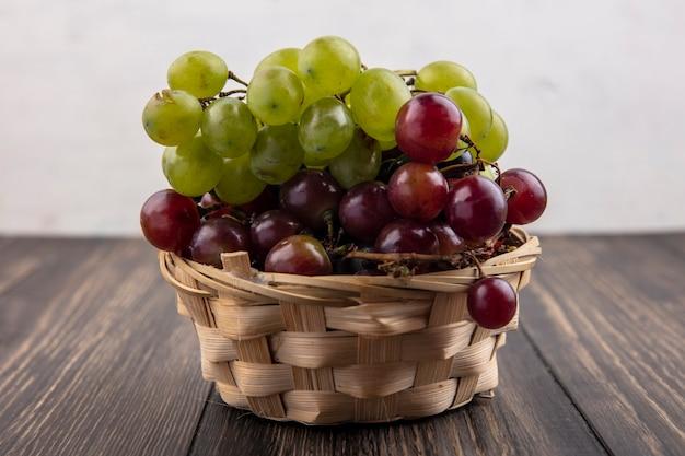 木製の表面と白い背景の上のバスケットのブドウの側面図 無料写真